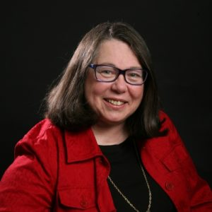 A woman in a red jacket and glasses